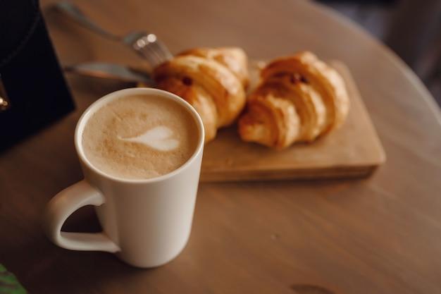 Cappuccino con bellissime latte art e croissant su una superficie di legno