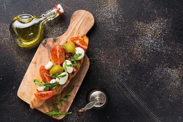 Bruschetta caprese toast con pomodorini, mozzarella, olive e basilico sulla vecchia superficie scura. vista dall'alto.
