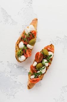 Bruschetta caprese toast con pomodorini, mozzarella, olive e basilico sulla vecchia superficie chiara del piatto bianco. vista dall'alto.
