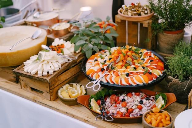 Caprese su un vassoio in tavola con insalata di formaggio e vasi di fiori con piante d'appartamento