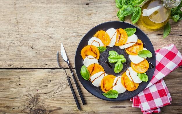 Insalata caprese fatta di mozzarella, pomodori gialli e foglie di basilico su uno sfondo di legno. vista dall'alto.