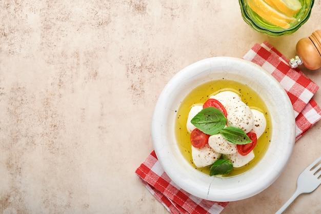 Insalata caprese. mozzarella con pomodorino al basilico in piatto di ceramica bianca e pomodoro ciliegino