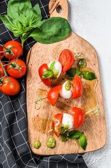 Insalata caprese su spiedino, pomodoro, pesto e mozzarella. merenda tartine. vista dall'alto