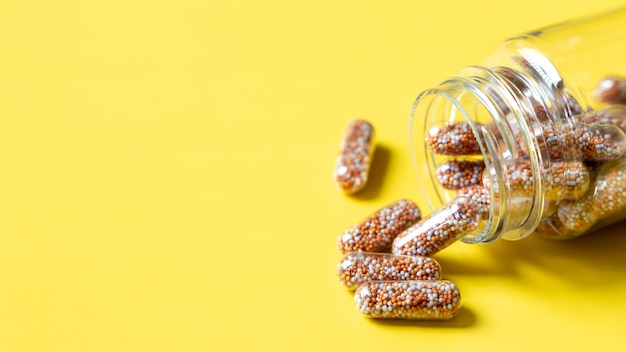 Capsule multivitaminici e integratori con frutta fresca e sana su sfondo giallo,