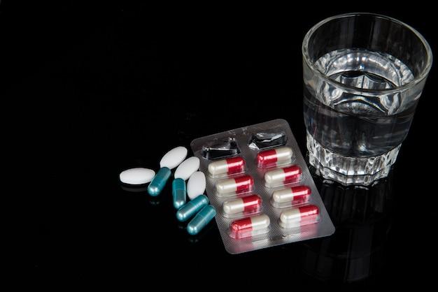Capsula e pillola farmaco con bicchiere d'acqua su sfondo nero