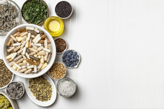 Capsule con integratori alimentari. ingredienti per integratori alimentari, minerali, olio ed erbe aromatiche in piatti