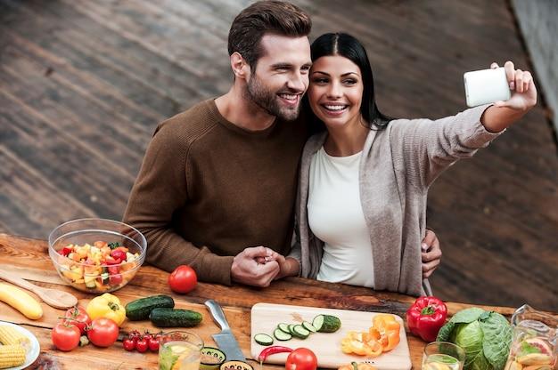 Catturare momenti luminosi insieme. vista dall'alto di una bella giovane coppia che fa selfie e sorride