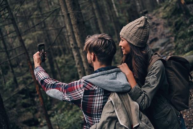 Catturare il momento. bella giovane coppia che prende selfie mentre fa un'escursione insieme nel bosco