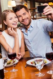 Catturare momenti romantici. bella giovane coppia di innamorati che fa selfie e sorride mentre si siede al ristorante insieme