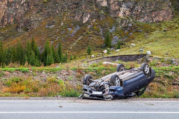 Luogo dell'incidente stradale su una curva, automobile rovesciata giace sul tetto, paraurti rotto, vetro, su una strada di montagna, orizzontale, spazio di copia