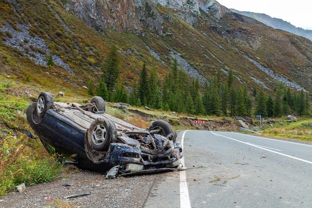 Luogo dell'incidente stradale in curva, auto ribaltata giace sul tetto