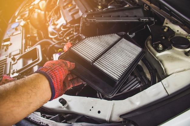 Il filtro dell'aria dell'automobile in una mano dell'uomo del meccanico sta installando nell'incavo del filtro dell'aria del motore di automobile, concetto automobilistico della parte.