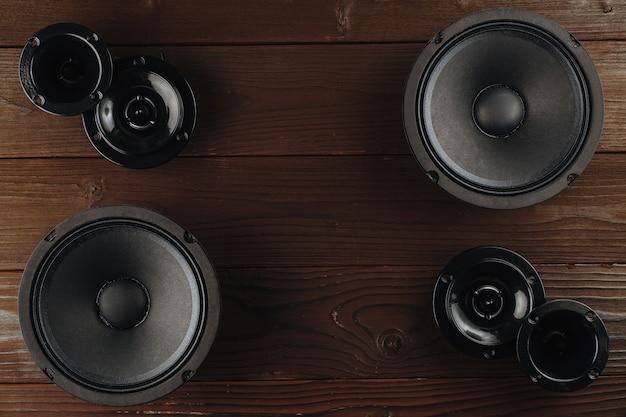 Audio per auto, altoparlanti per auto nere giacciono su una superficie di legno marrone.