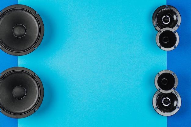 Gli altoparlanti per auto audio per auto giacciono in fila su uno spazio di copia di sfondo blu