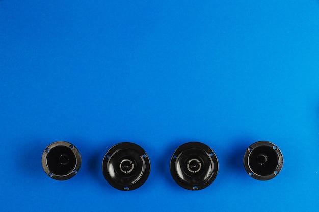 Gli altoparlanti per auto audio per auto giacciono in fila su uno sfondo blu con spazio di copia