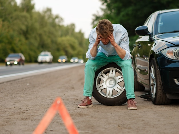 Guasto all'auto, uomo stanco seduto sulla ruota di scorta