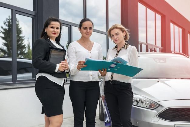 Procedura acquisto auto. rivenditore donna con tablet e acquirenti con cartella in piedi vicino all'auto