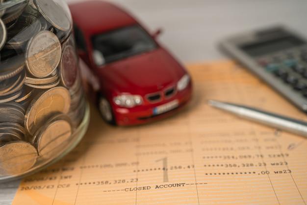 Auto e calcolatrice con monete sullo sfondo della banca del libro prestito auto finanziamento risparmio di denaro