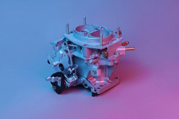 Carburatore per auto per motore a combustione interna per la miscelazione dell'aria con un sottile spruzzo di combustibile liquido illuminato con luce blu e rossa. parti automobilistiche.