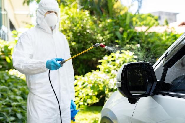 Pulizia dell'auto utilizzando spray chimico alcolico per disinfettare e decontaminare il coronavirus covid-19