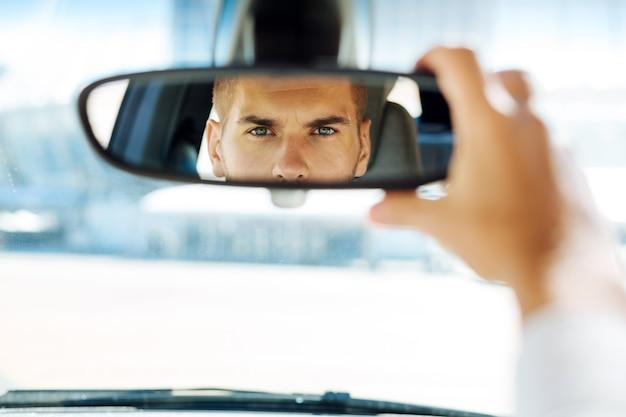 Nell'automobile. primo piano di uno specchietto retrovisore con un pilota abile intelligente esaminandolo