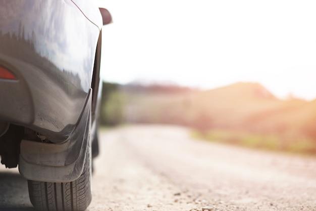 Un'auto su una strada di campagna e polverosa sullo sfondo del tramonto