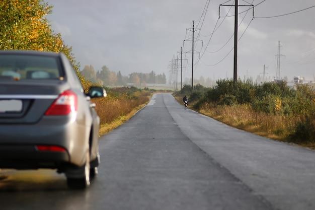 Auto sulla corsia della strada di campagna in una piovosa giornata autunnale