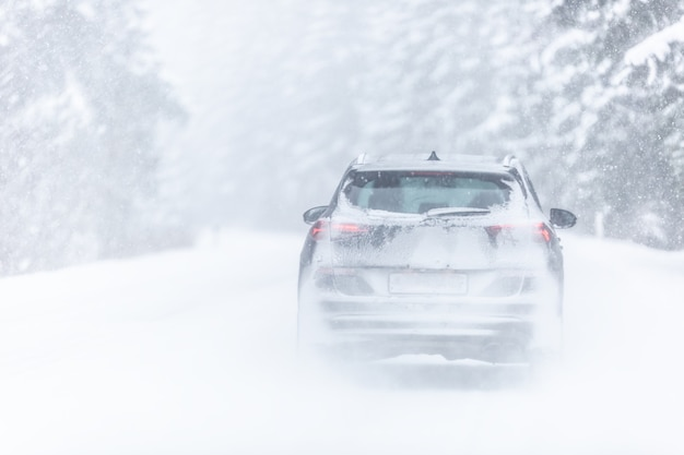 Auto coperta di neve che guida nella tempesta di neve in una fredda giornata invernale nella foresta.