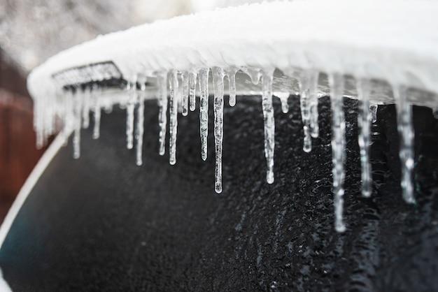 Auto ricoperta di ghiaccio e ghiaccioli dopo la pioggia gelata maltempo gelido ciclone tempesta di ghiaccio scene di neve invernale