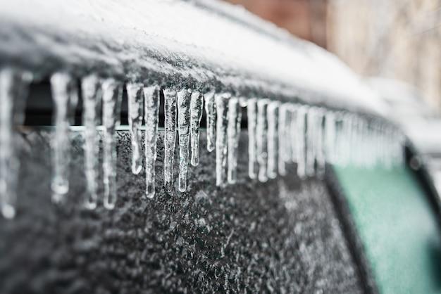 Auto ricoperta di ghiaccio e ghiaccioli dopo la pioggia gelata tempesta di ghiaccio di maltempo invernale scene gelide