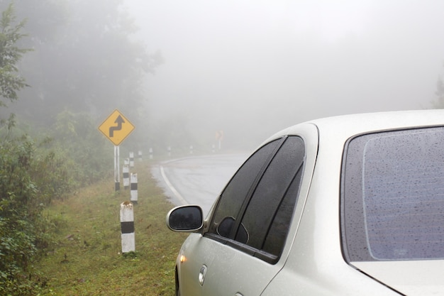 Auto su una strada curva in caso di pioggia e nebbia