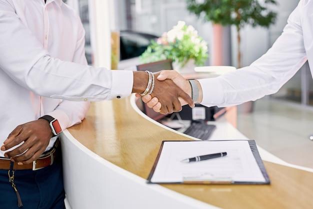 Il concessionario e il cliente di auto si stringono la mano