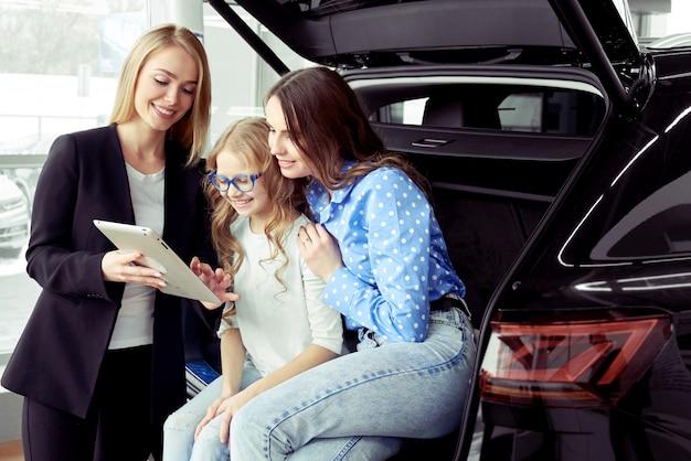 Donna consultantesi del commerciante di automobile con la figlia nel salone automatico