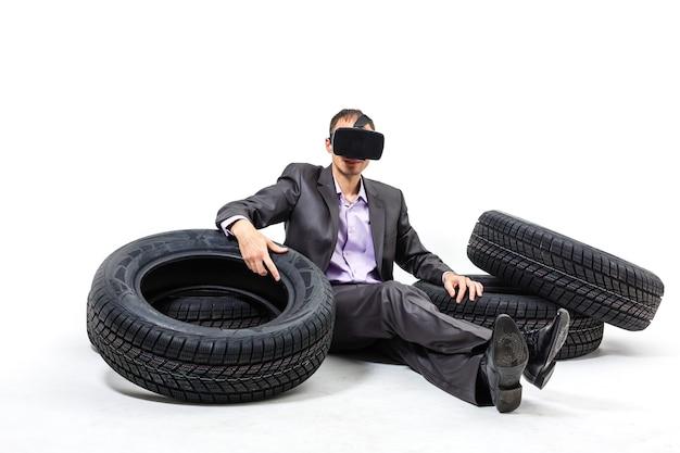 Uomo del concessionario di auto con occhiali virtuali che tengono pneumatici per auto su sfondo bianco