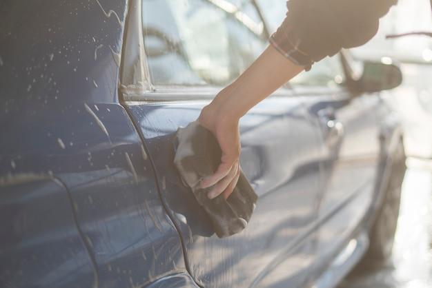 Un'auto che dettaglia, chiuda la mano che tiene una spugna e pulisce l'auto
