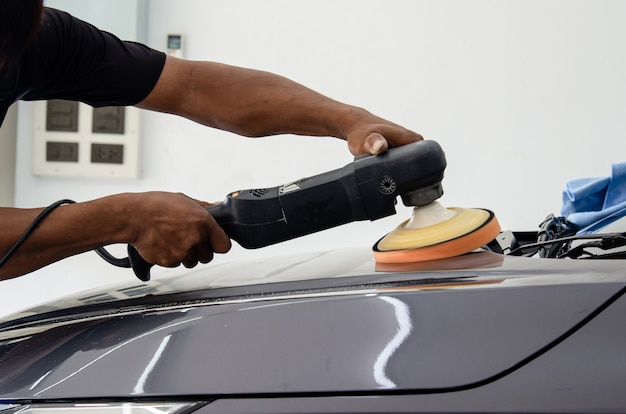 Dettagli auto - meccanico maschio che tiene la lucidatrice per auto. industria automobilistica, officina di lucidatura e verniciatura e riparazione auto.