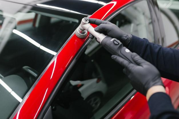 Dettagli auto - uomo con lucidatrice orbitale in officina per lucidare auto. messa a fuoco selettiva.