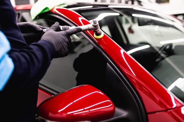 Dettagli auto - uomo con lucidatrice orbitale nell'officina di lucidatura auto. messa a fuoco selettiva.