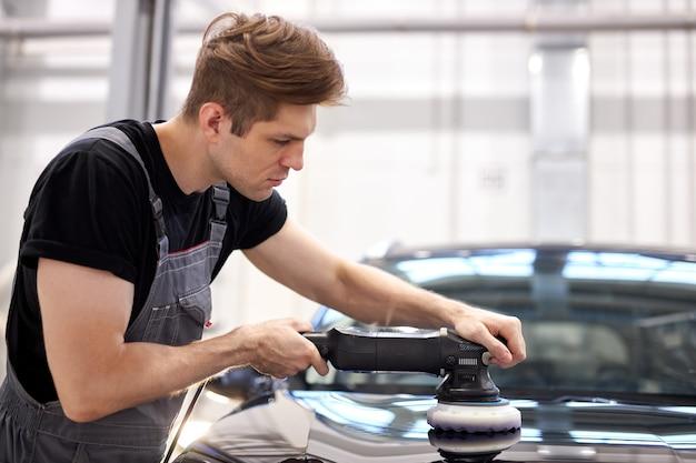 Concetto di dettaglio e lucidatura dell'auto. giovane lavoratore di sesso maschile di servizio auto professionale