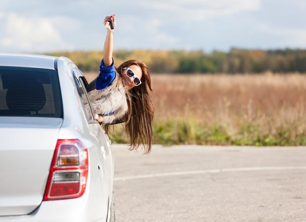 Donna conducente di automobile che mostra le chiavi della macchina nuove sorridente