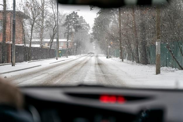 L'auto guida su una strada invernale in una bufera di neve. vista interna. l'auto davanti è andata in un cumulo di neve