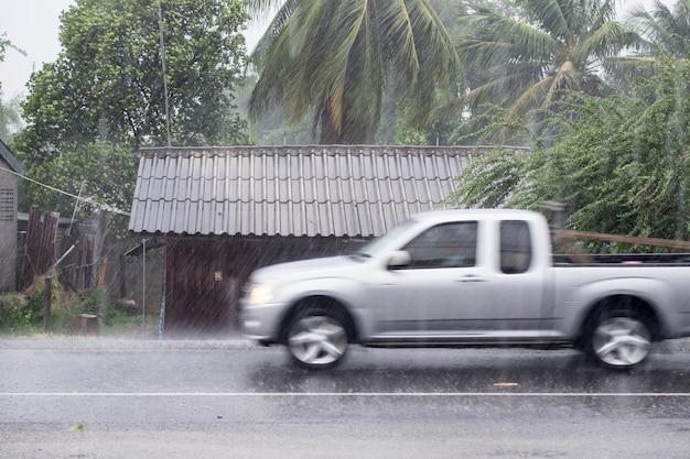 Movimento di guida dell'auto attraverso la pioggia di burrasca sulla casa di legno anteriore in strada rurale