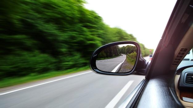 Auto che guida attraverso la strada vuota e concentrati sullo specchio