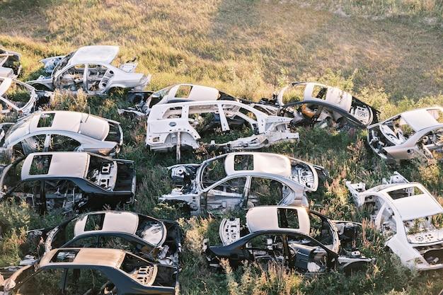 Auto discarica rotte vecchie auto arrugginite sdraiate sull'erba