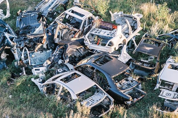 Auto scarica un mucchio di vecchie auto rotte marce nella vista dall'alto del campo