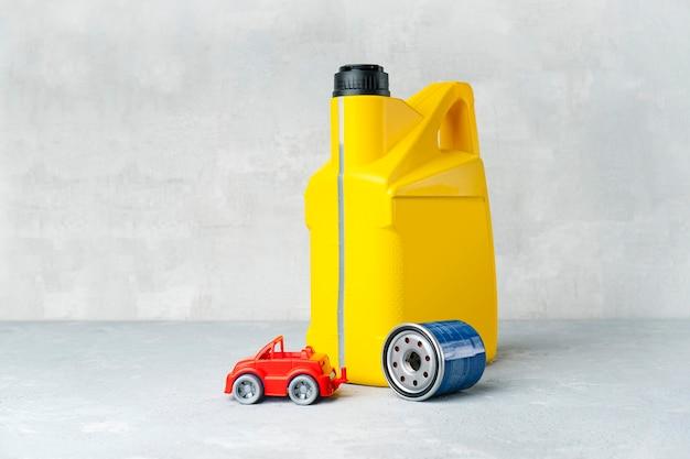 Concetto di cambio olio motore auto con tanica olio giallo, filtro olio e piccola automobile