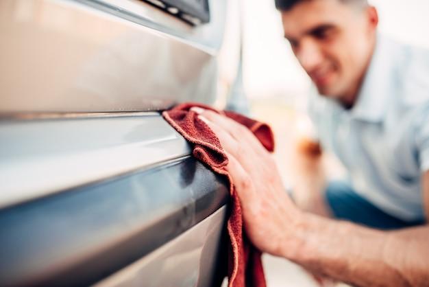 Lucidatura esterna auto su stazione di autolavaggio. l'uomo sfregamento paraurti del veicolo con smalto per automobili