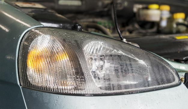 I fari dell'automobile si chiudono sull'immagine con le gocce di pioggia come fondo