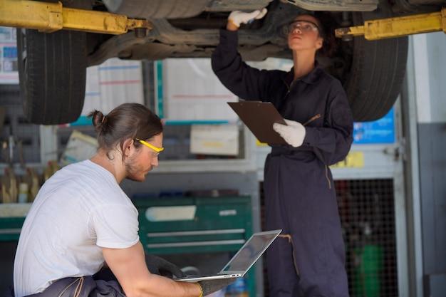 Ispezione auto con laptop da tecnici specializzati, concetto di tecnologia