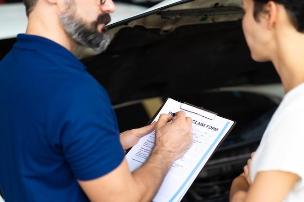 Concetto di assicurazione auto. l'agente assicurativo esamina l'auto danneggiata con le informazioni di scrittura della donna sul modulo di reclamo.